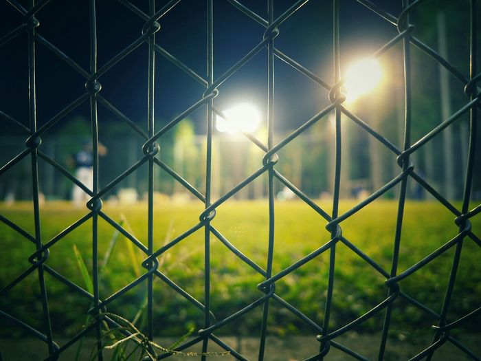 Illuminated baseball diamond seen through chainlink fence