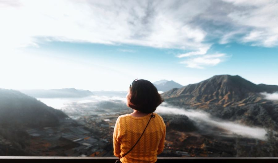 Rear view of woman standing by railing against mountains and sky