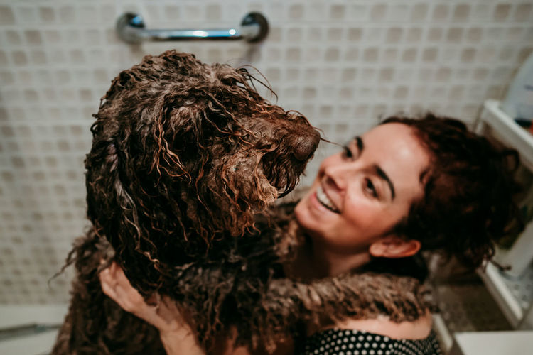 High angle view of smiling woman with dog in bathroom