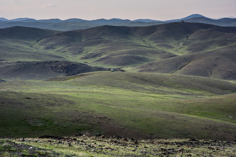 A single car parked hillside in mongolias vast landscape amid lush green hills.
