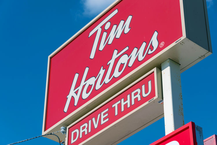 Tim Horton sign or symbol in blue sky. The franchise is one of the most successful and popular in Canada Architecture Building Exterior Built Structure Cafeteria City Drive Thru Franchise Information Information Sign Logo Ontario Ontario, Canada Popular Shop Shopping Sightseeing Sign Silhouette Symbol Tim Hortons  Toronto Toronto Canada Tourism Travel Urban