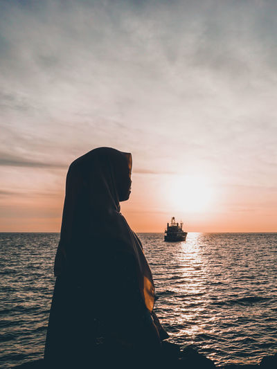 Woman wearing hijab looking away while sitting by sea against sky during sunset
