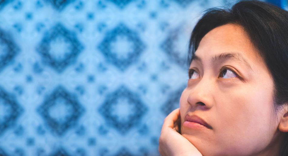 Close-Up Of Thoughtful Woman Against Wall