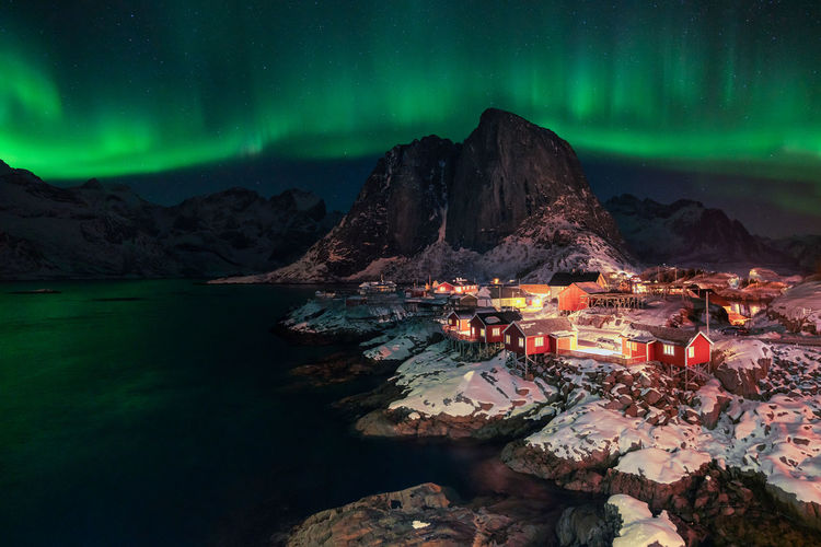 Illuminated buildings by mountain against sky at night during winter