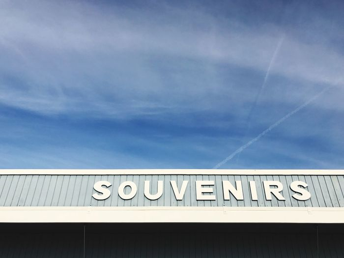 Low Angle View Of Souvenirs Text On Building Against Blue Sky