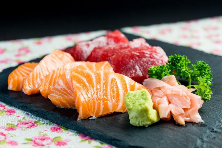 Close-up of sashimi on slate at table
