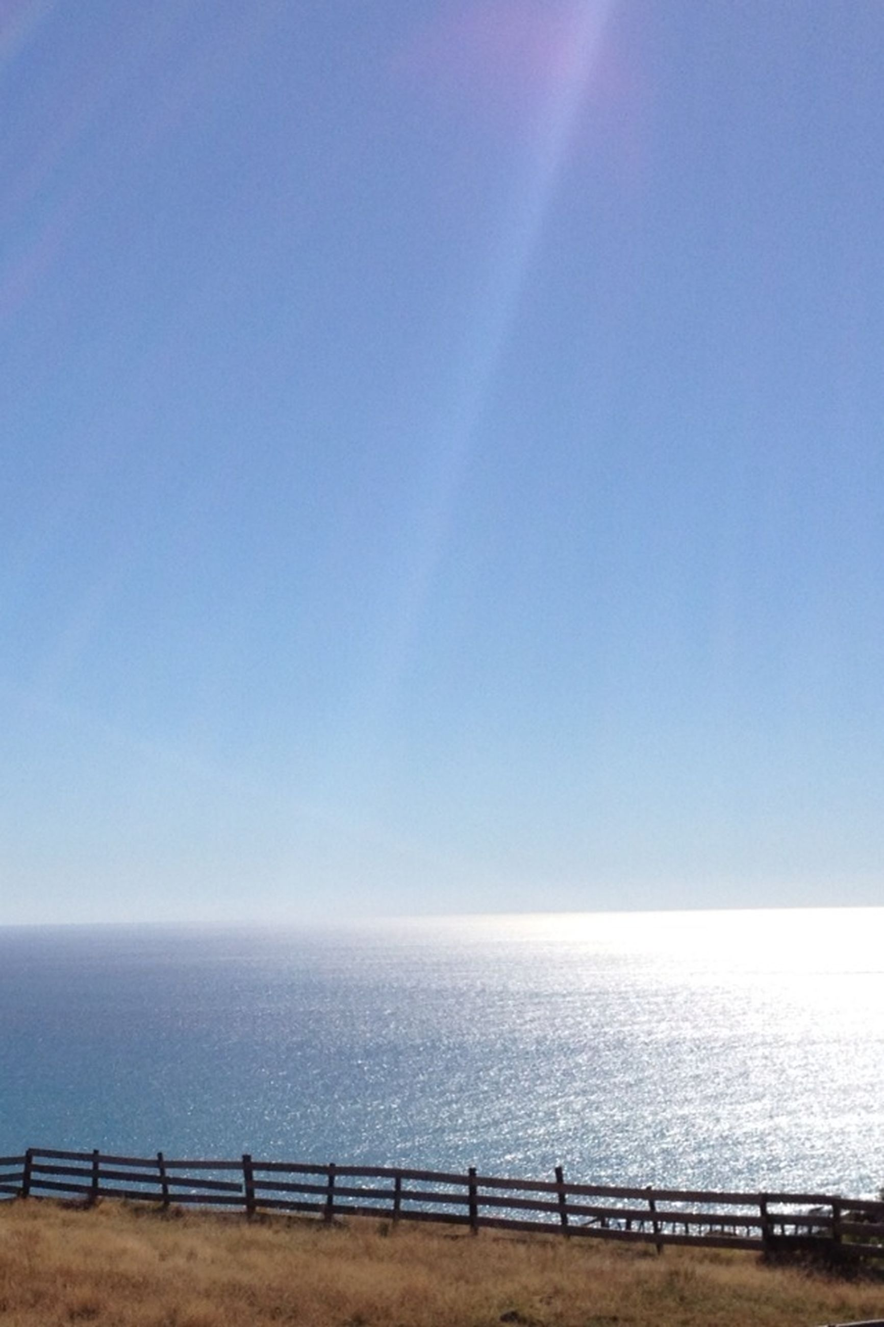 sea, horizon over water, water, scenics, tranquil scene, tranquility, beauty in nature, beach, blue, clear sky, railing, copy space, nature, idyllic, shore, sky, sunlight, outdoors, calm, remote