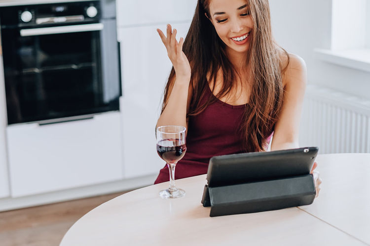 Young woman using phone while sitting on table at home