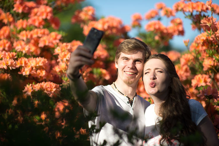 Happy friends taking selfie against flowering plants in park