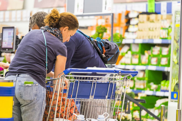 Couple of adult people family concept buying food and more at the mall market - daily life for usually people Shopping Cart Two People Supermarket Store Shopping Retail  Women Customer  Couple - Relationship Adult Men Rear View Lifestyles Consumerism Standing Choice Focus On Foreground Indoors  Casual Clothing Heterosexual Couple Groceries Buying Hairstyle Family Young Adult Caucasian Diary Economy Together