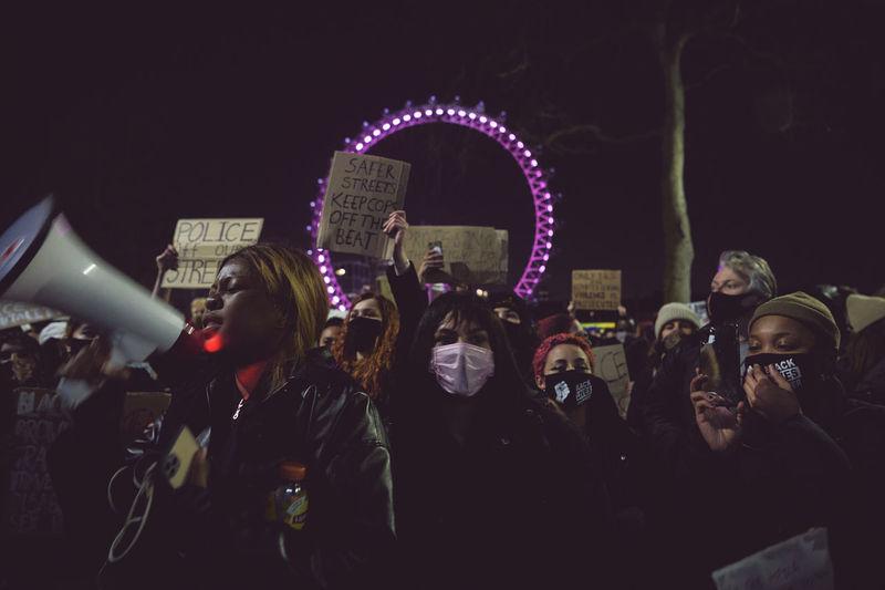 People photographing illuminated ferris wheel at night