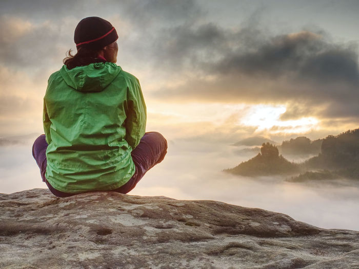 Young active woman with trekking equipment sitting, relaxing and looking at far misty mountains