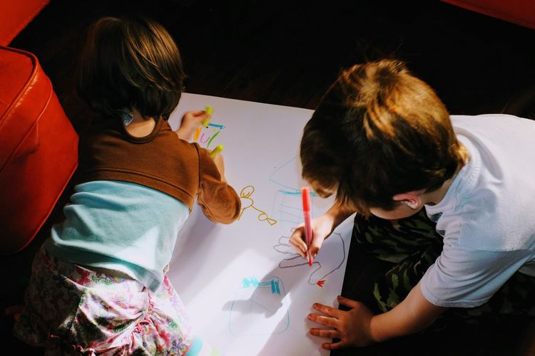 High Angle View Of Kids Drawing On Paper At Home