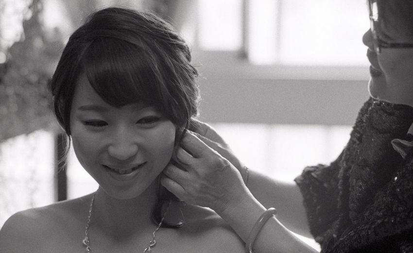 Stylist assisting woman with hairstyle