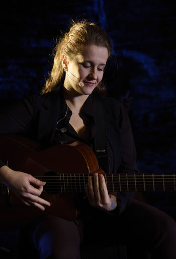 Woman playing guitar while sitting on stage