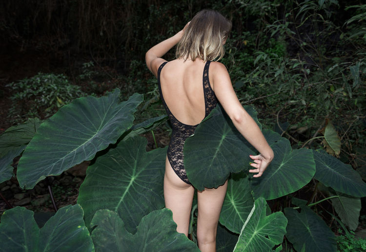 Rear view of woman standing amidst plants