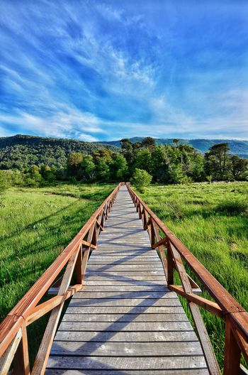 Wooden jetty on landscape against sky