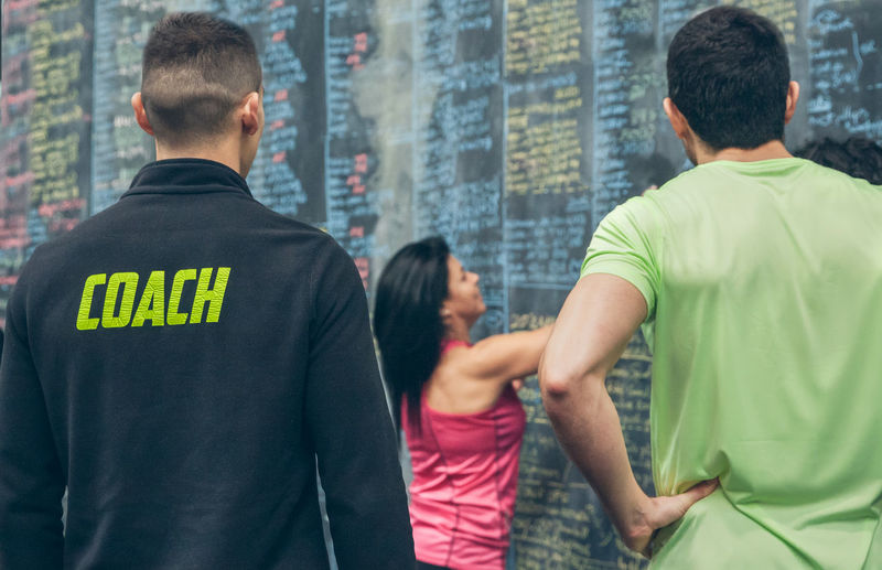 Rear view of people standing against graffiti