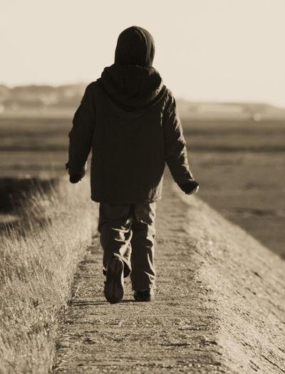Full Length Rear View Of Boy Walking On Groyne