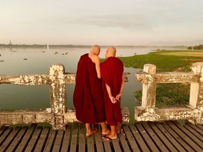 Rear view of monks standing by railing against sea and sky