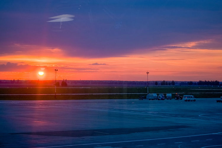 Sky Sunset Cloud - Sky Transportation Orange Color Mode Of Transportation Nature No People Beauty In Nature Airplane Scenics - Nature Air Vehicle Street Land Vehicle Airport Illuminated Airport Runway Dusk Road Street Light Outdoors