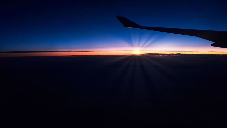 Silhouette airplane against sky during sunset