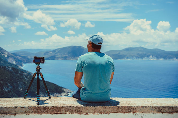 Rear View Of Man Sitting By Camera On Retaining Wall While Looking At Sea Against Sky