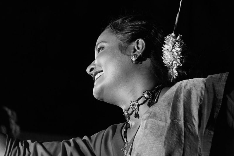 Low angle view of smiling mid adult woman wearing traditional clothing dancing in room