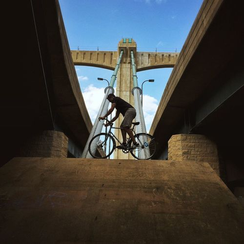 Low angle view of man balancing on bicycle along bridge