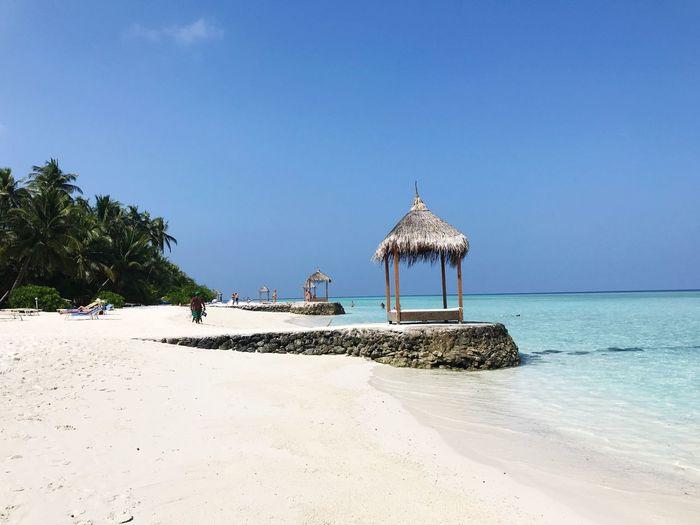 Hut on beach against clear blue sky
