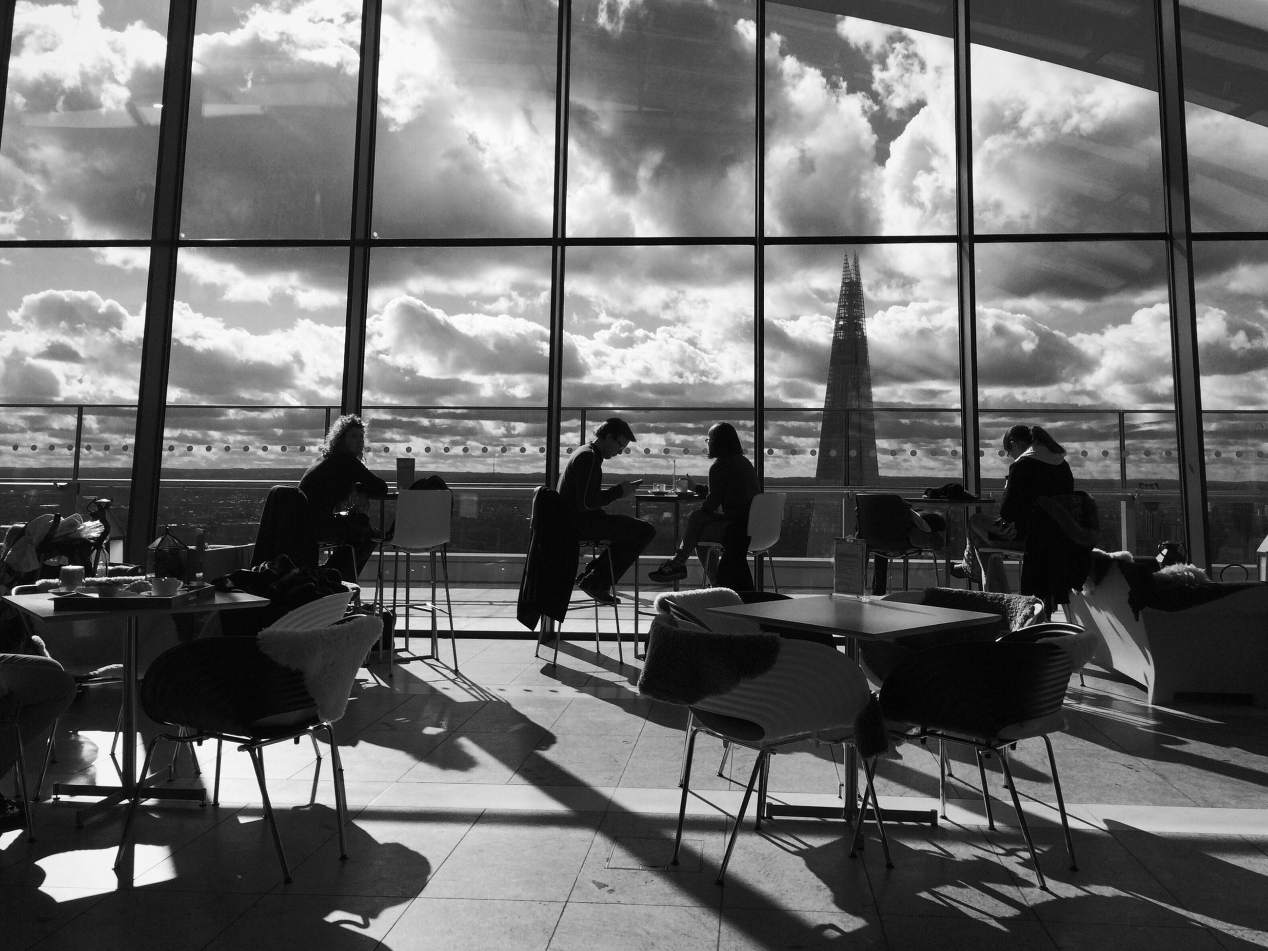 indoors, chair, table, sitting, window, restaurant, glass - material, sky, men, empty, relaxation, transparent, person, cloud - sky, seat, airport, lifestyles, day, silhouette