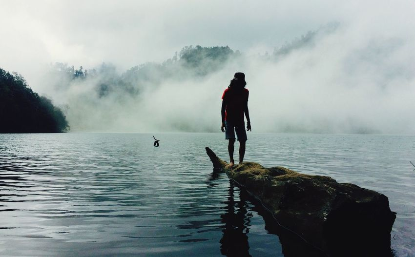 Man standing on log over ranu kumbolo lake during foggy weather