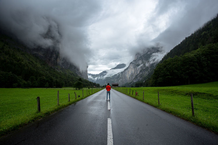 Rear view of man standing on road amidst mountains against sky