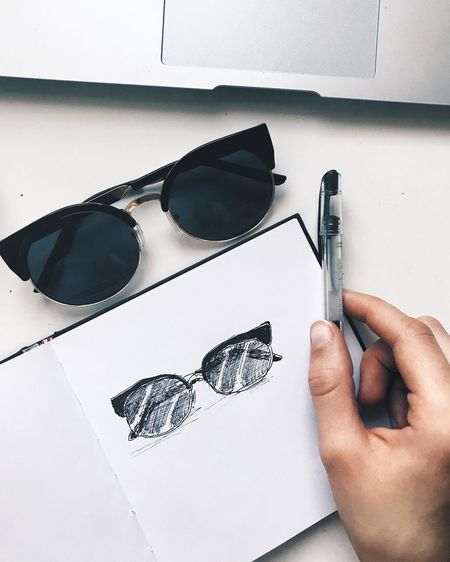 Close-Up Of Hand With Sunglasses Drawing In Book On Table