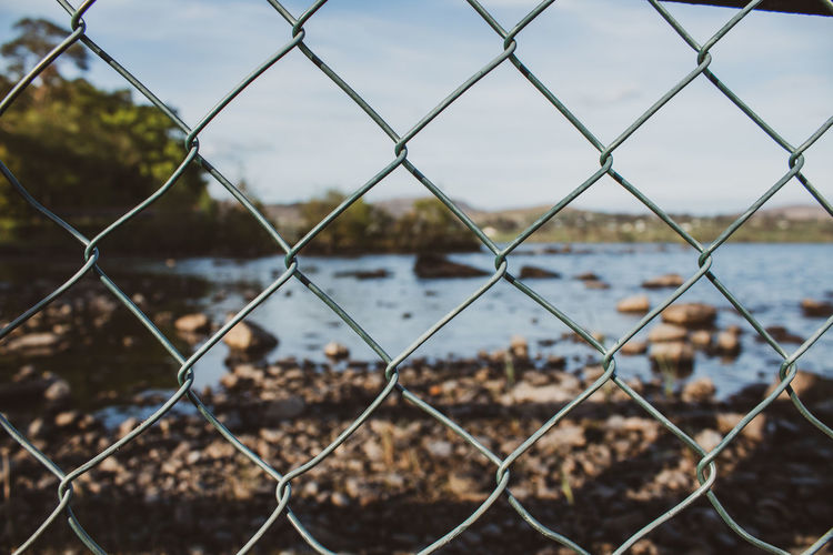 Close-up of chainlink fence against lake and sky in ireland
