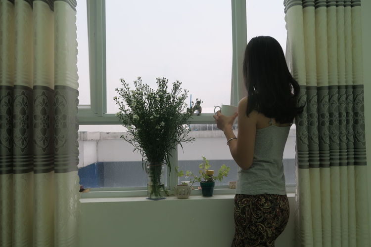 Side View Of Woman Having Drink While Looking Through Window At Home