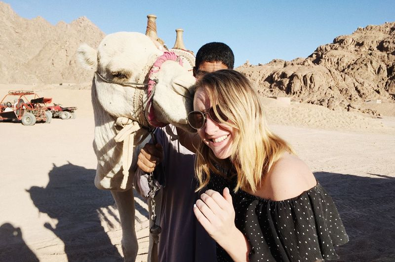 Happy Woman With Camel At Desert