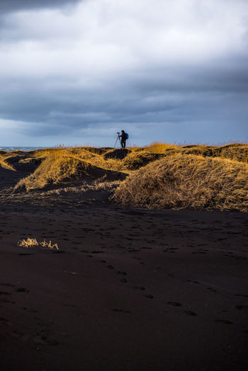 Full length of man standing photographing on land against sky