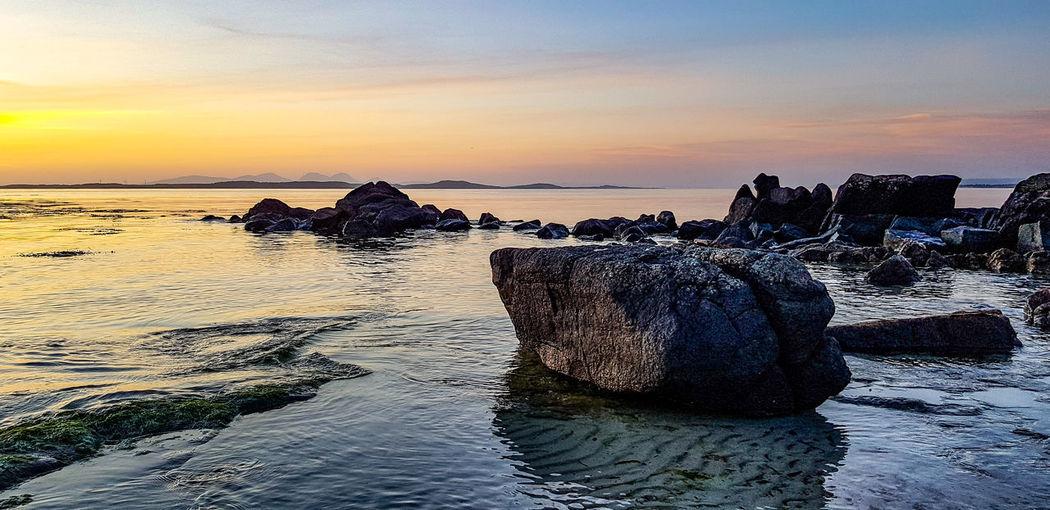 Rocks on beach against sky during sunset
