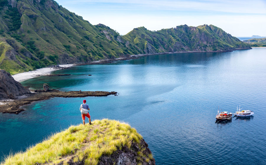 Young Hiker Standing Alone on Cliff Mountain, Enjoy the View Of Padar Island Before National Park, Indonesia Field Green Color INDONESIA Mountain View Top Tourist Trekking Walking Around Boat Hiker Hikers Island Mountain Nature Outdoors Padar Padar Island Pulau Route Tranquility Traveler Water
