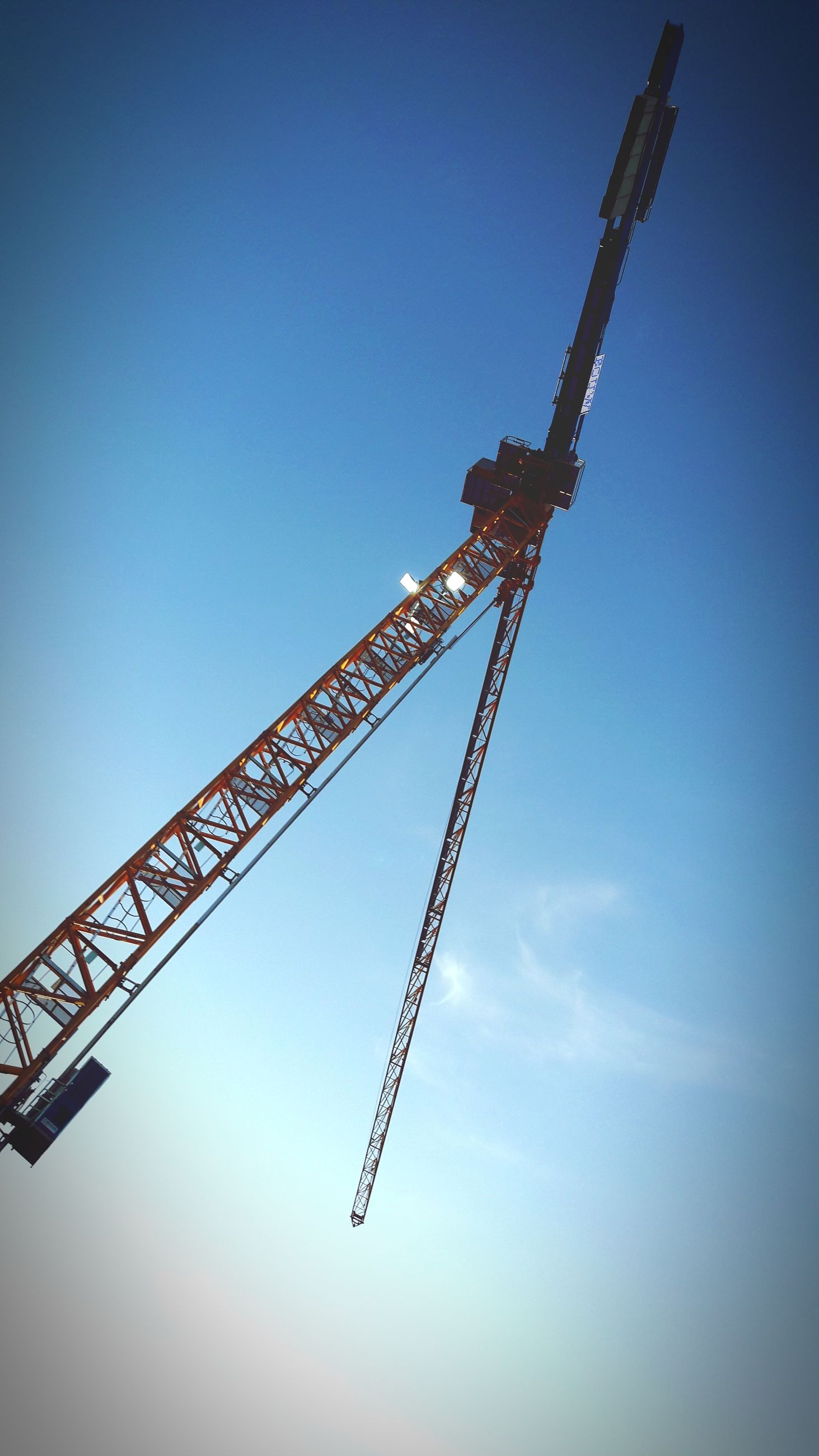 construction site, crane - construction machinery, development, construction, low angle view, industry, crane, copy space, no people, construction machinery, day, progress, blue, clear sky, outdoors, sky