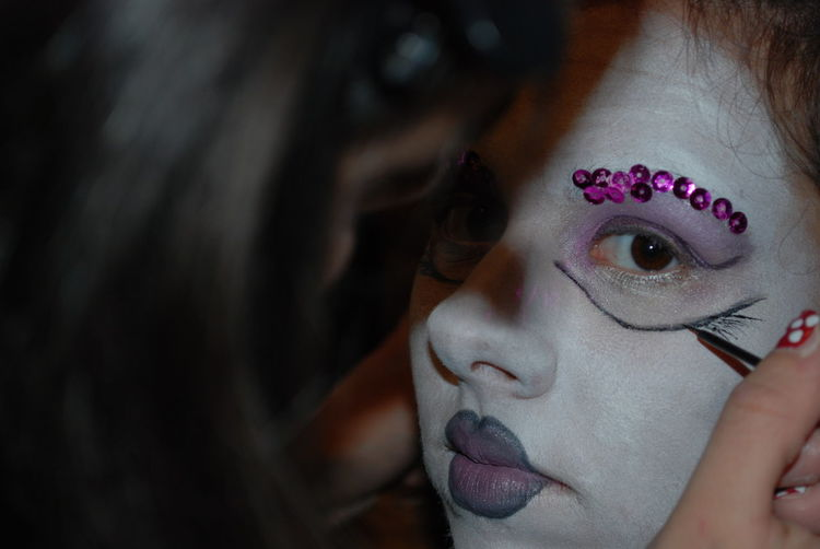 Cropped image of artist applying make-up to woman