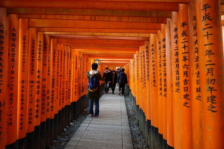 Narrow walkway along orange pillars with japanese script