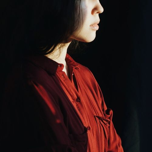Close-up of woman looking away over white background