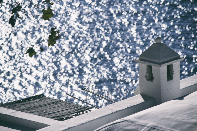 High angle view of house roof sea during sunny day