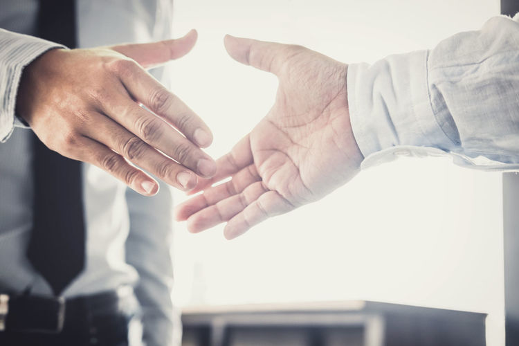Midsection of business colleagues shaking hands while standing in office