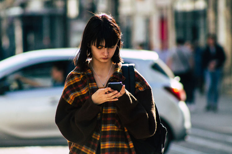 Young woman using mobile phone in city