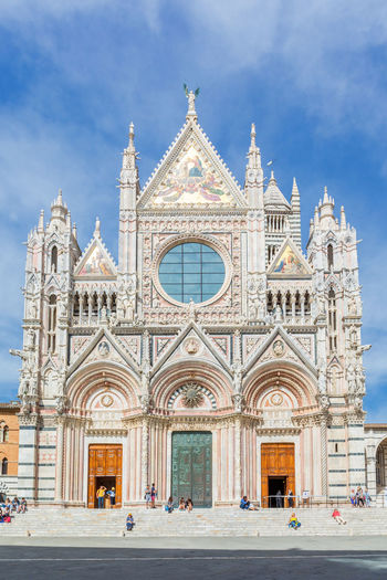 Duomo di siena cathedral with tourists on the stairs in siena, italy