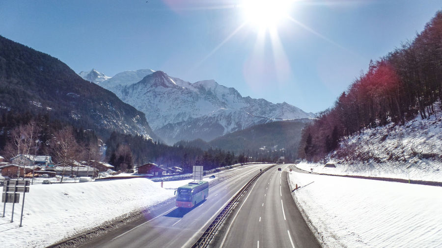 Snow Winter Cold Temperature Transportation Road Sky Mountain Nature Sunlight Scenics - Nature Beauty In Nature Sun Mountain Range Lens Flare Sunbeam Day Environment Motor Vehicle Car No People Diminishing Perspective Snowcapped Mountain Outdoors Bright