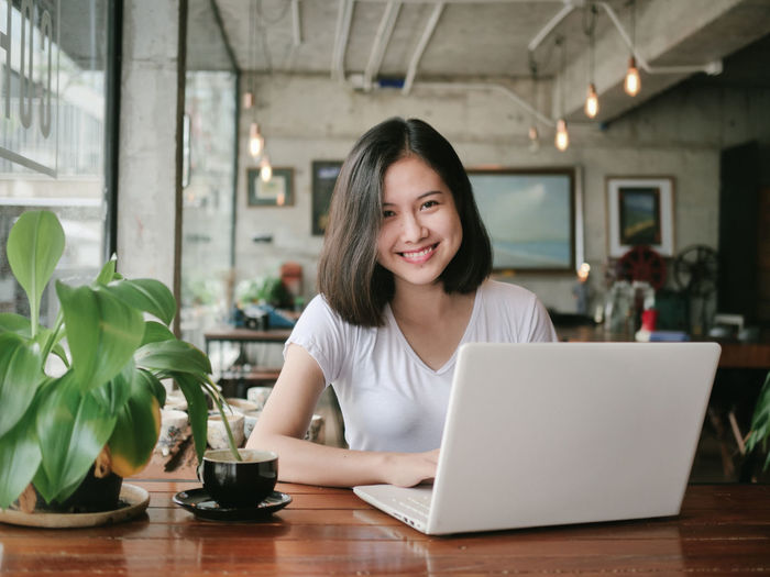 Portrait Of Smiling Young Businesswoman Using Laptop On Table At Cafe